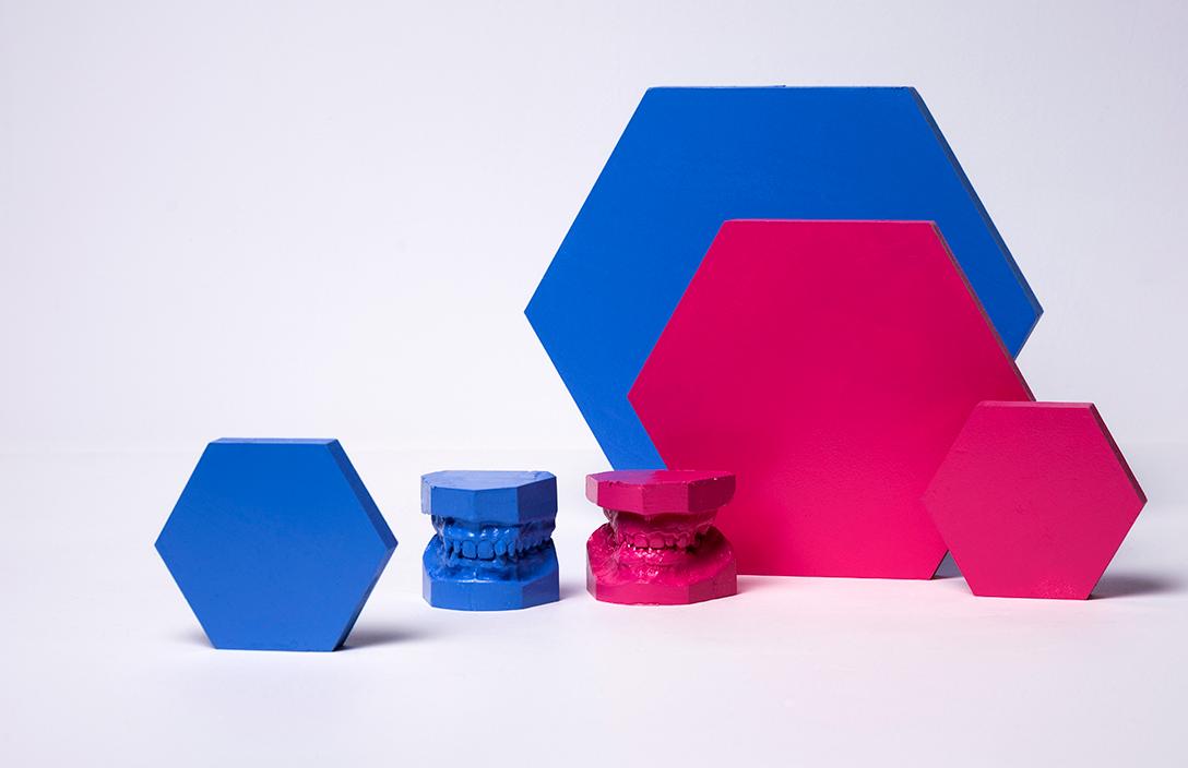 niebiesko różowe odlewy szczęki oraz 4 przestrzenne geometryczne, różowe i niebieskie figury, ustawione na białym tle