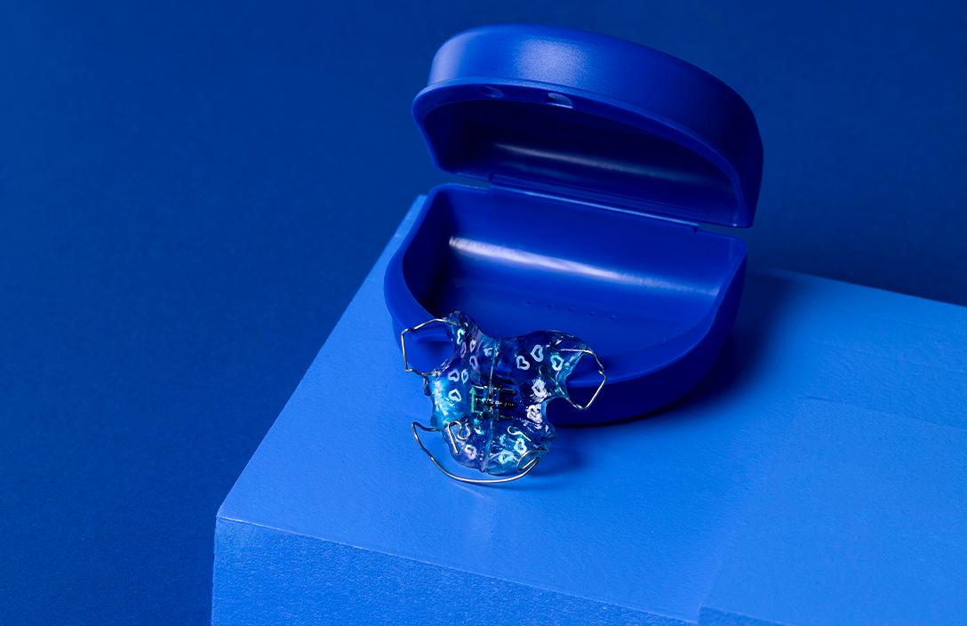 niebieski aparat ortodontyczny w serduszka, oparty o niebieskie etui na aparat ortodontyczny